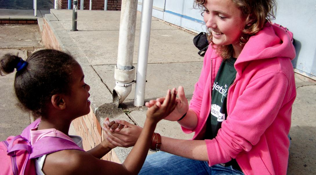 Global Gap Year programme volunteer plays a game with a child during her project in South Africa